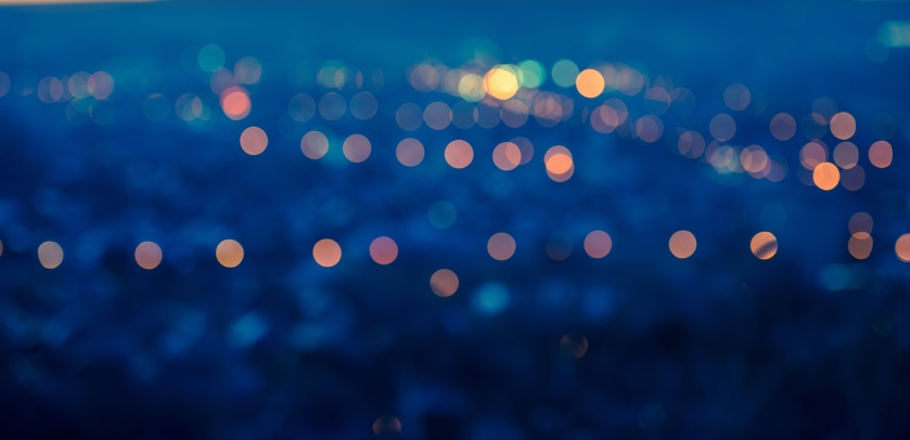 panorama city blurring lights abstract circular boken blue background with twilight horizon, closeup