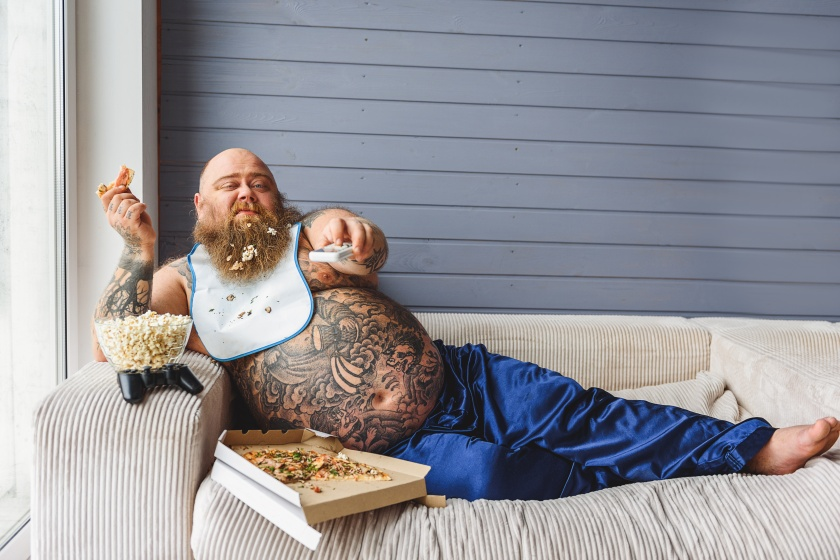Relaxed thick guy entertaining with pizza and television